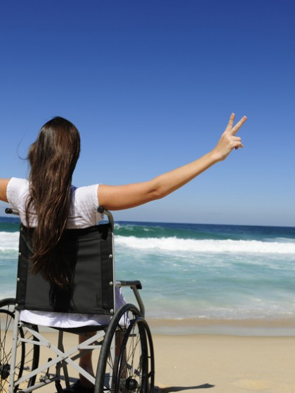 happy disabled woman in wheelchair outdoors beach showing victory sign