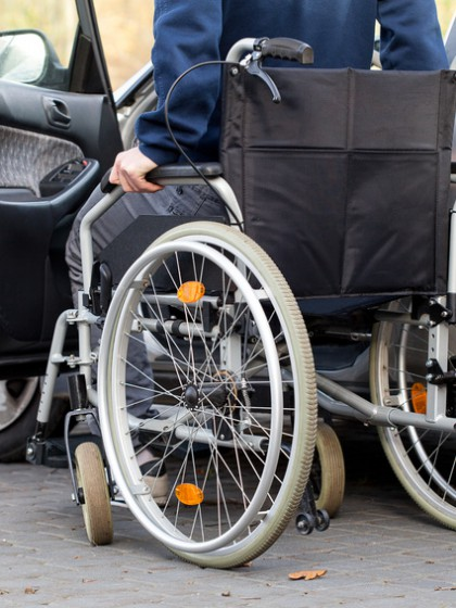 A disabled driver using a wheelchair entering his car